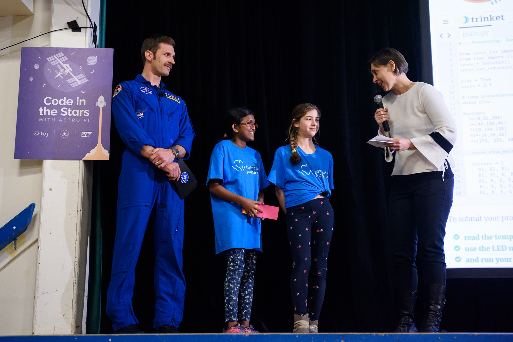 Kids asking their question to the astronaut on stage.