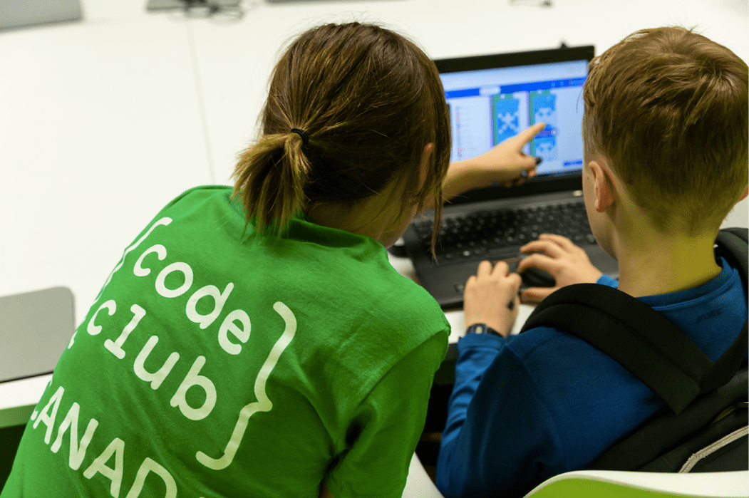A Code Club volunteer guides a coder through a project.