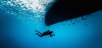 Scuba diver under a boat with fish.
